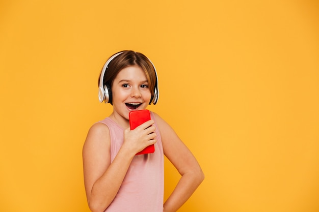 Happy girl looking aside while using heeadphones and singing in smartphone isolated