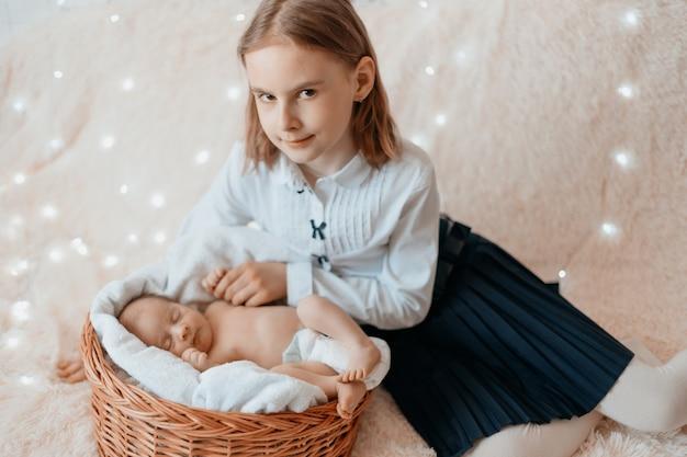 그녀의 갓난 여동생을 바라보는 행복한 소녀