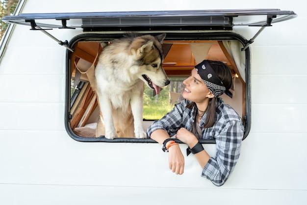 열린 창에서 허스키 개를 보고 행복 한 소녀
