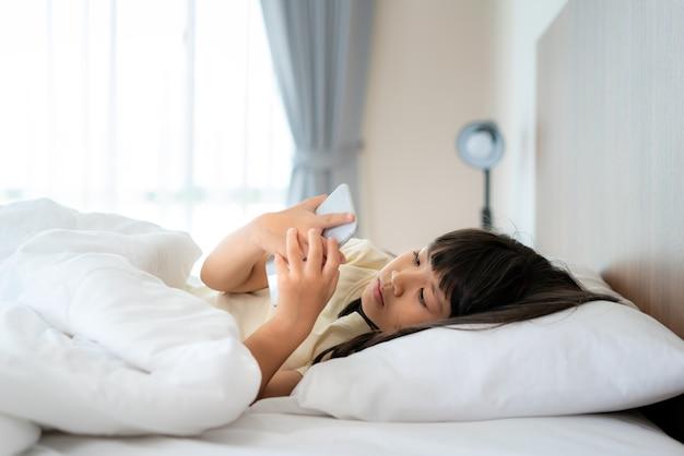 Счастливая девушка, глядя на мобильный телефон, лежа на кровати в спальне у себя дома утром после пробуждения, готовясь пойти в школу.