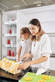 Счастливая девушка смотрит на мать, режущую кусок сладкого бисквитного рулета, который они сделали вместе