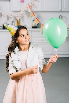 Happy girl looking at green balloon in kitchen