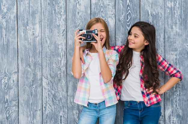 Happy girl looking at her friend looking through vintage camera standing against wooden wall