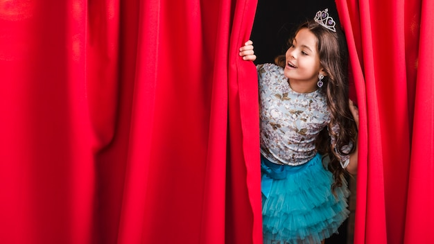 Happy girl looking through red curtain on stage