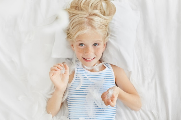 Happy girl looking with blue eyes, throwing feathers from pillow in air, having excited expression. small naughty girl not wanting to sleep in kindergarten. funny little kid having cheerful look