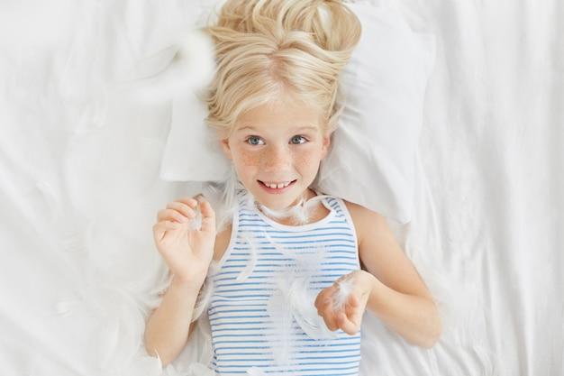 Счастливая девушка смотрит с голубыми глазами, бросая перья из подушки в воздух, взволнованное выражение. маленькая непослушная девочка, не желающая спать в детском саду. забавный маленький ребенок с веселым взглядом