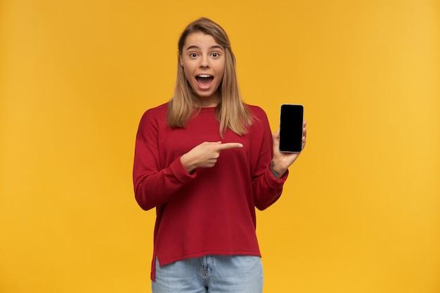 幸せな女の子は驚いて見える、興奮して口を大きく開いて、携帯電話を手に持って、黒い画面をカメラに向け、人差し指でそれを指さす