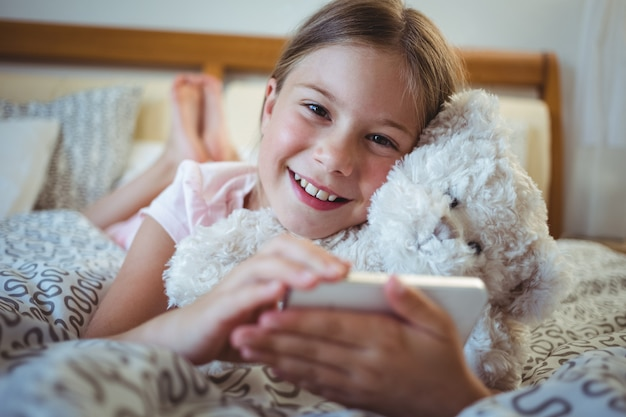 Happy girl lying on bed with a teddy bear and using mobile phone