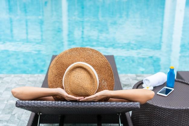 プールサイドでリラックスしてサンベッドに横たわって幸せな女の子。夏、休日のコンセプト。閉じる
