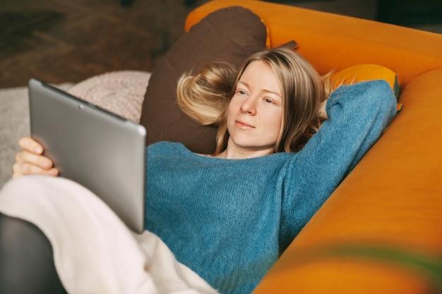 タブレットで映画を見ながら、リビングルームの快適なソファに横になっている幸せな女の子
