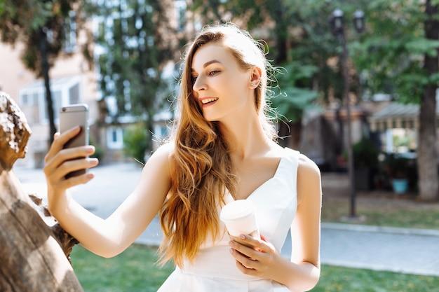 Счастливая девушка делает селфи в парке