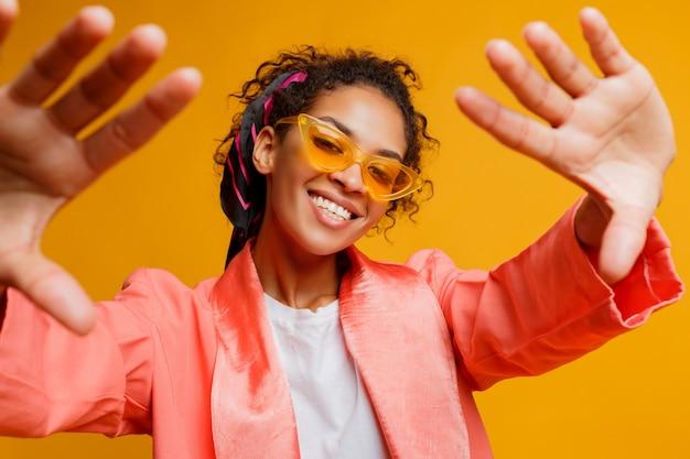 スタジオで黄色の背景にセルフポートレートを作る幸せな女の子。トレンディな春のルック。