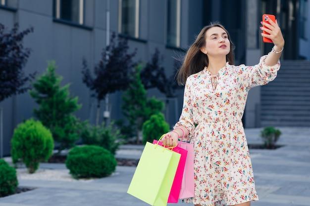 야외 모바일 스마트 폰으로 selfie를 만드는 행복 한 소녀. 쇼핑을 하 고 재미 사회적 영향력 여자입니다. 차세대 청소년 라이프 스타일 사람과 기술의 개념.