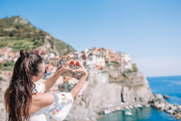 Happy girl making with hands heart shape on the old coastal village in cinque terre national park.