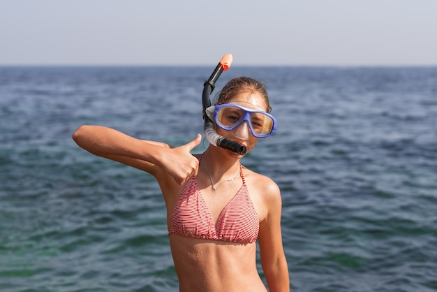 Happy girl in mask and snorkel on the beach