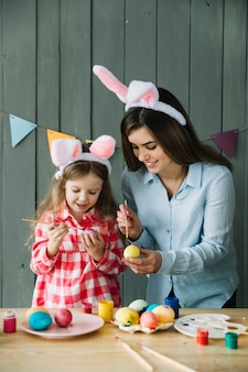 Happy girl and mother in bunny ears painting eggs for easter