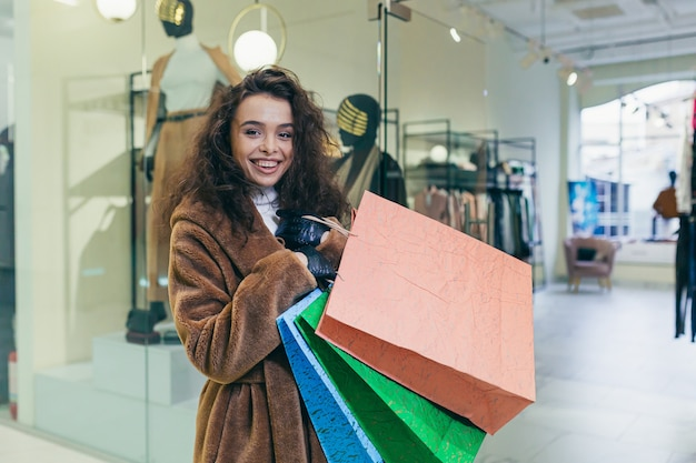 Happy girl near a clothing store, holding packages with goods