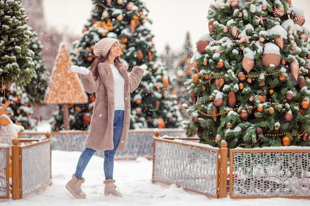 Happy girl near fir-tree branch in snow for new year.