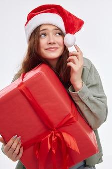 Счастливая девушка новогодний подарок в руках новогодняя шапка санта-клауса. фото высокого качества Premium Фотографии