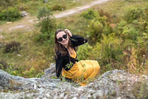 돌 바위의 배경에 행복 한 소녀. 여름 시간