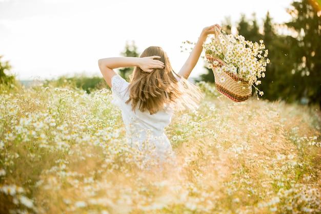 カモミールフィールド、夏の日没の幸せな女の子。白いドレスを着ています。走ったり回転したり、髪の毛の風、ライフスタイル。自由の概念と暑い夏。