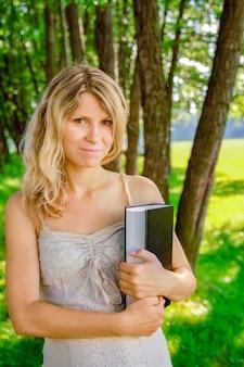 Счастливая девушка на природе читает книгу в парке