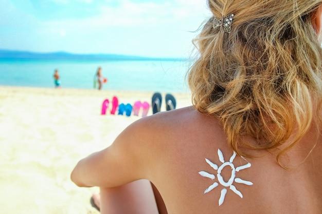 Счастливая девушка на море с изображением солнца на спине