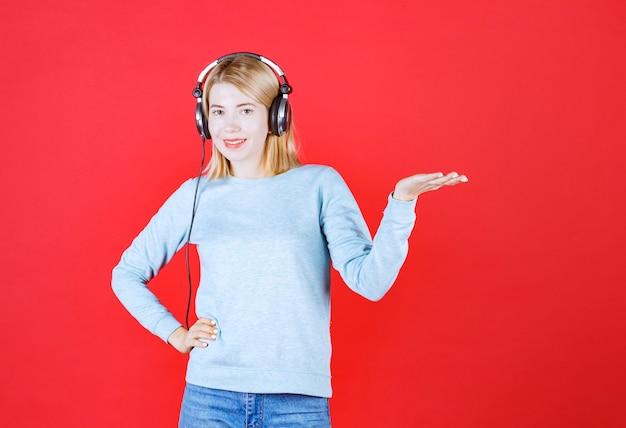 Счастливая девушка открытая рука, как ладонь, пока слушает музыку с наушником