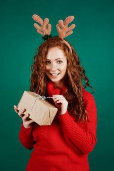 스튜디오 촬영에서 크리스마스 선물을 열어 행복 한 여자
