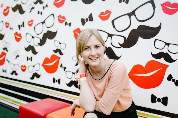 Счастливая девушка или женщина на цветном фоне очков и усов в стильной развлекательной комнате. время вместе в развлекательном центре. понятие радости.