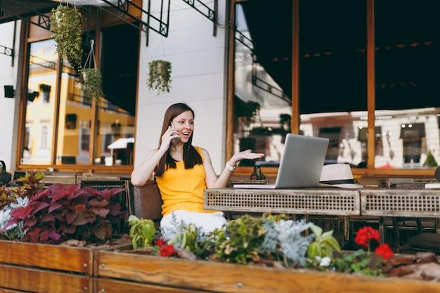 Ragazza felice in caffè di strada all'aperto seduto al tavolo con computer pc portatile, parlando al telefono cellulare, conducendo una piacevole conversazione, nel ristorante durante il tempo libero