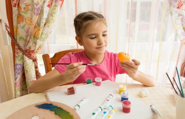 Счастливая девушка рисует пасхальные яйца за столом на кухне