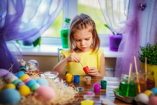 Happy girl painting easter eggs, small child at home have fun. spring holiday