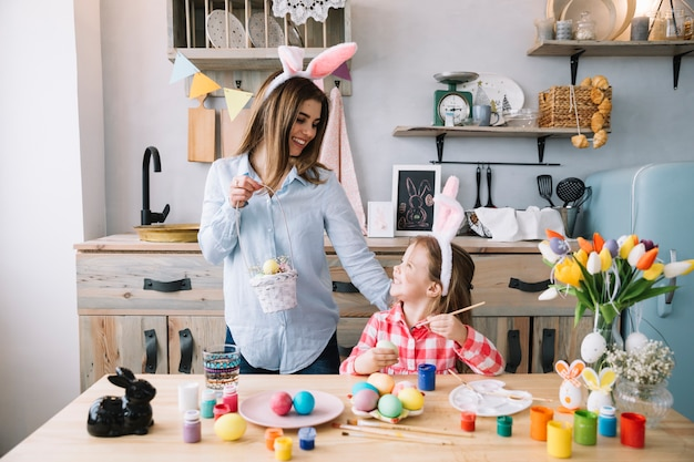 Happy girl painting eggs for easter near mother with basket