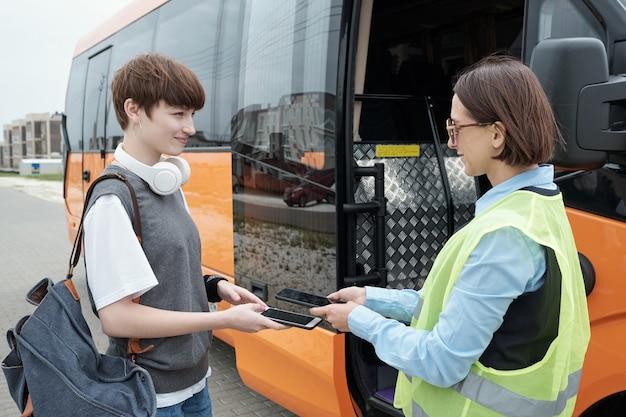 Счастливая девушка-пассажир, держащая смартфон под планшетом молодой женщины-кондуктора автобуса