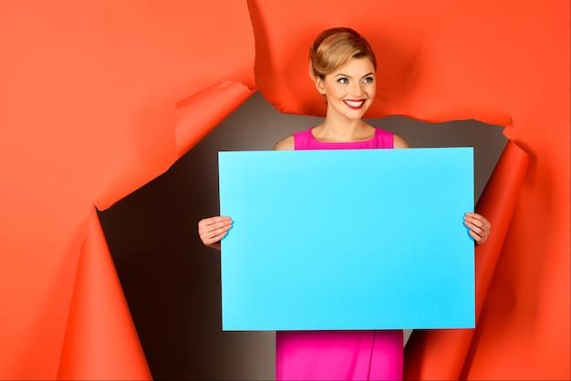 Счастливая девушка проходит через отверстие в красной бумаге. чувственная блондинка в розовом платье держит пустую синюю доску для вашего текста. скопируйте место для рекламы. модная одежда. модные товары. распродажа.