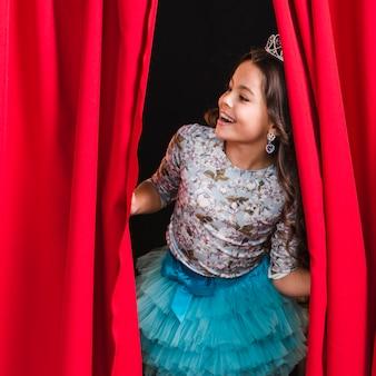Счастливая девушка заглядывает из красной занавески на сцене