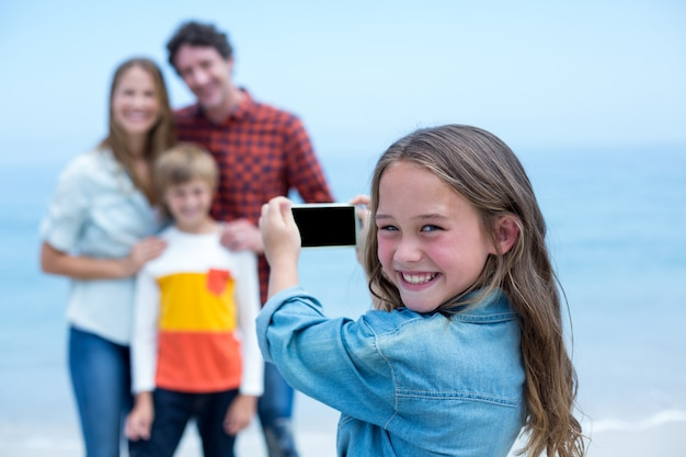 Happy girl photographing family with mobile phone