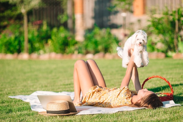 Happy girl on picnic plays with white puppy on green grass in the park