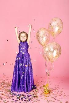 Happy girl in pink dress celebrating