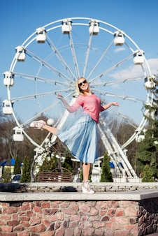 Happy girl in a pink sweater and a blue flying skirt poses against of a park and rides.