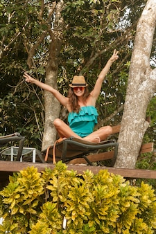 Happy girl on platform at the tree with sunbeds