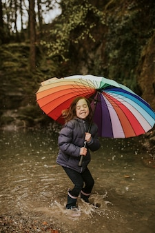 Happy girl playing by the forest lake with an umbrella on a rainy day