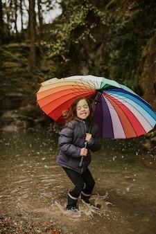 雨の日に傘をさして森の湖で遊ぶ幸せな女の子