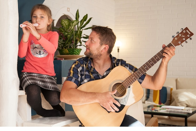 Happy girl playing the flute next to her father