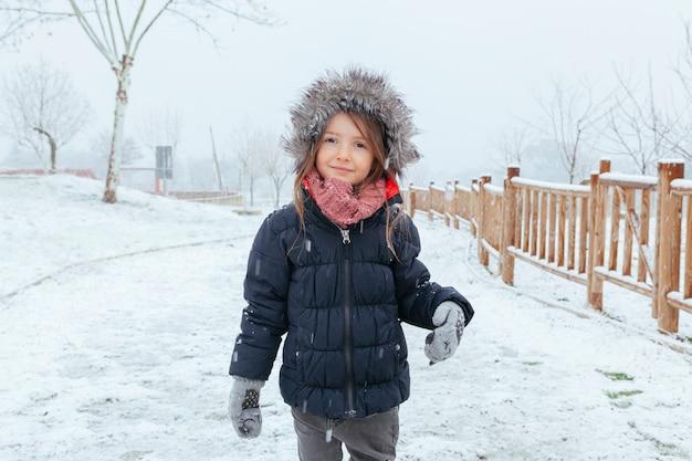 Счастливая девушка играет на улице со снегом