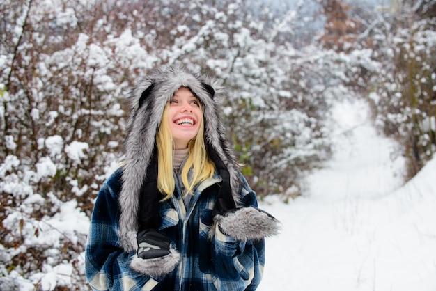 따뜻한 코트 모피 모자와 장갑에 눈 겨울 날 겨울 휴가 아름 다운 여자를 재생 하는 행복 한 소녀