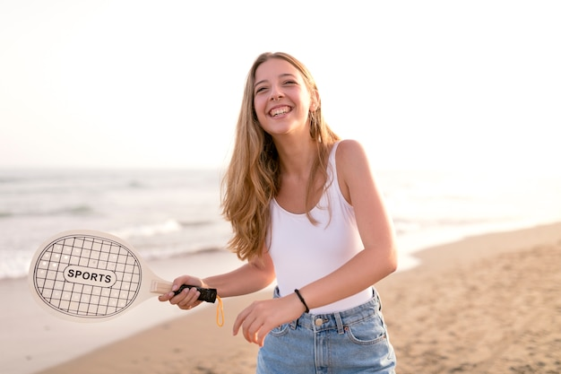 Happy girl playing tennis at beach
