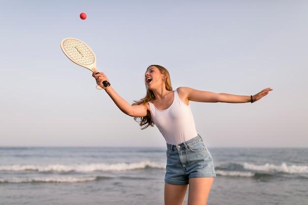 Ragazza felice che gioca a tennis vicino al mare