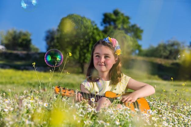 Happy girl playing ukulele in summer field